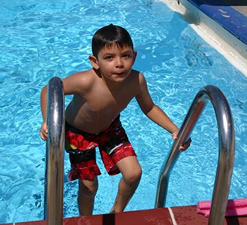 Child exiting pool on pool ladder.