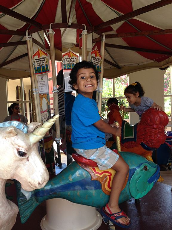 Child on Childrens Museum merry-go-round at Itty Bitty Camp